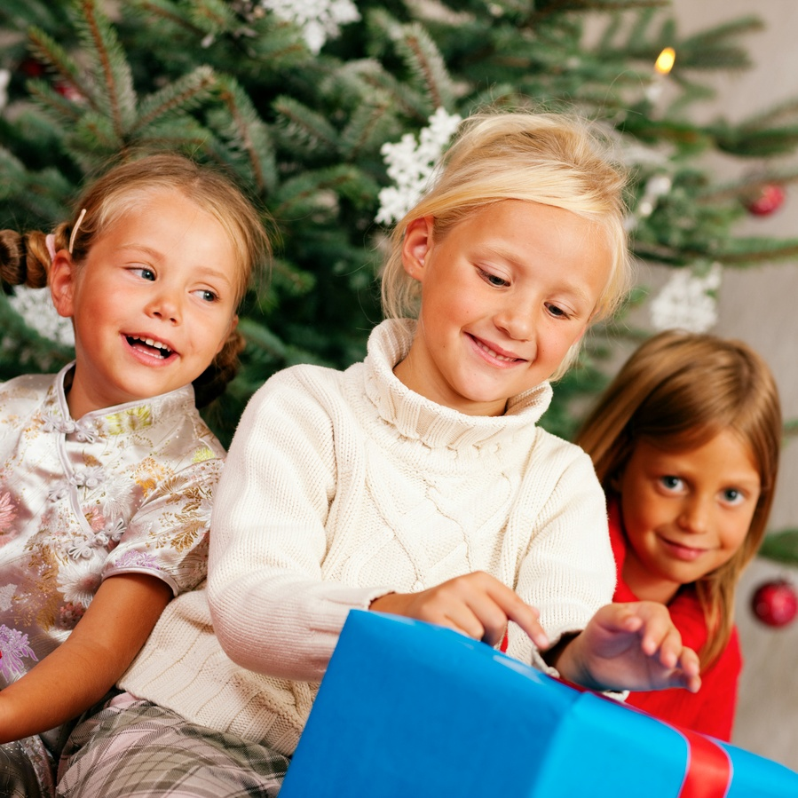 Kids in front of Christmas tree with gifts
