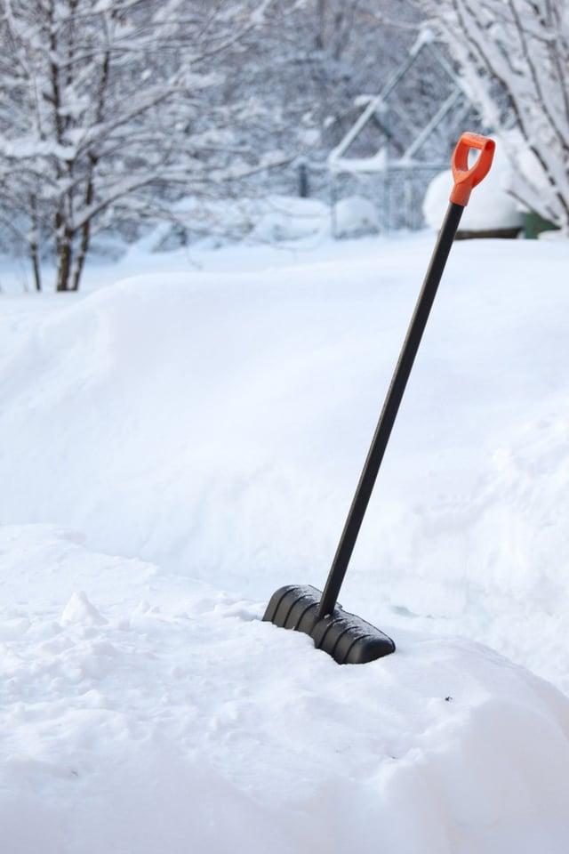 Snow shovel in deep snow bank