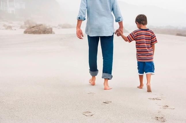 Parent holding child's hand walking on beach