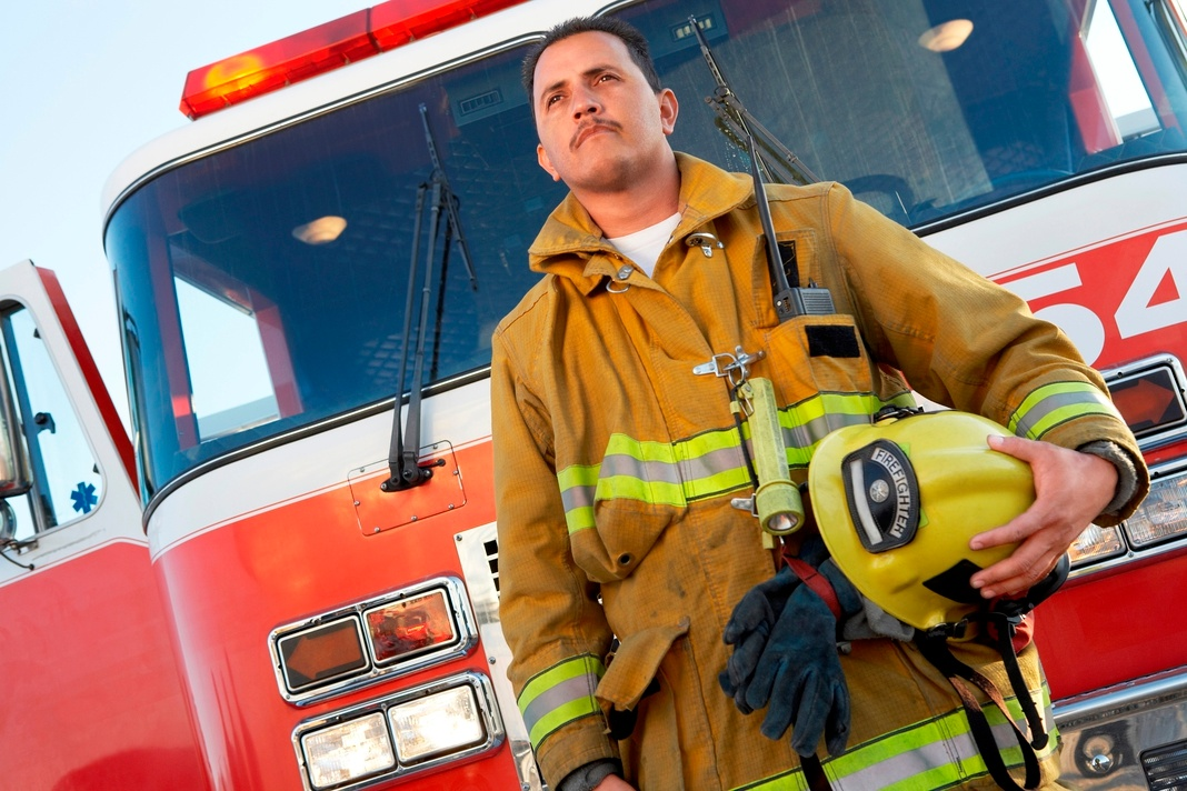 Firefighter next to fire engine with siren