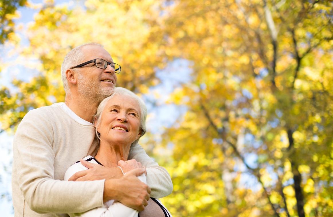 mature couple enjoying fall leaves