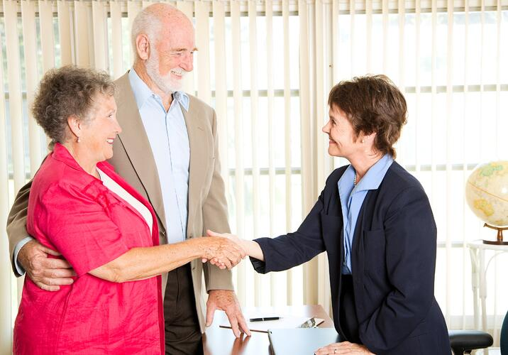 elderly couple shaking hands with personal injury lawyer