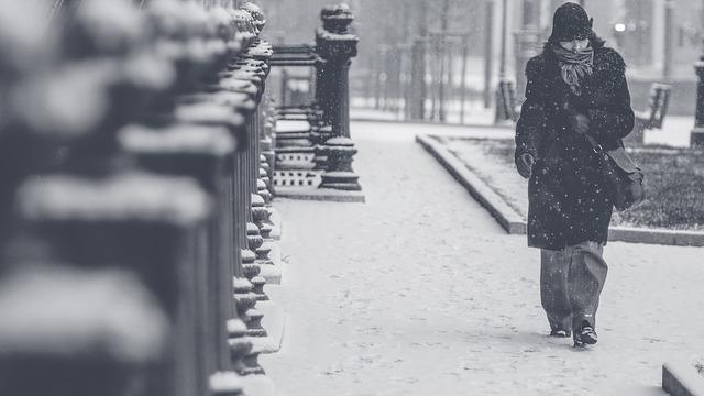 woman walking in blizzard on street