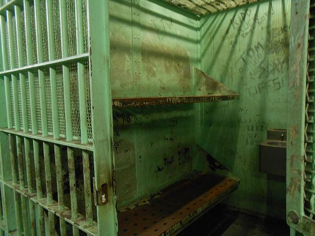 Prison or jail cell with bars and door open