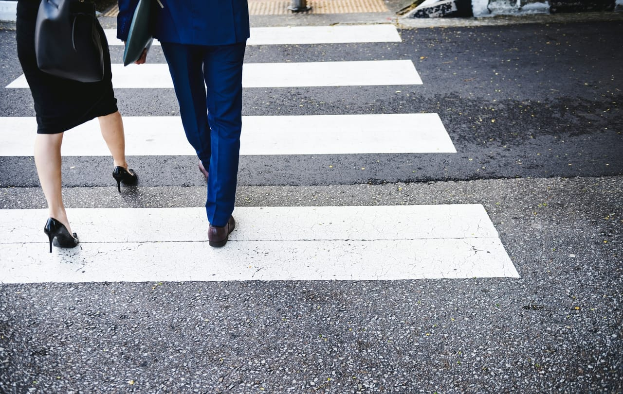 man-and-woman-crossing-street-in-crosswalk
