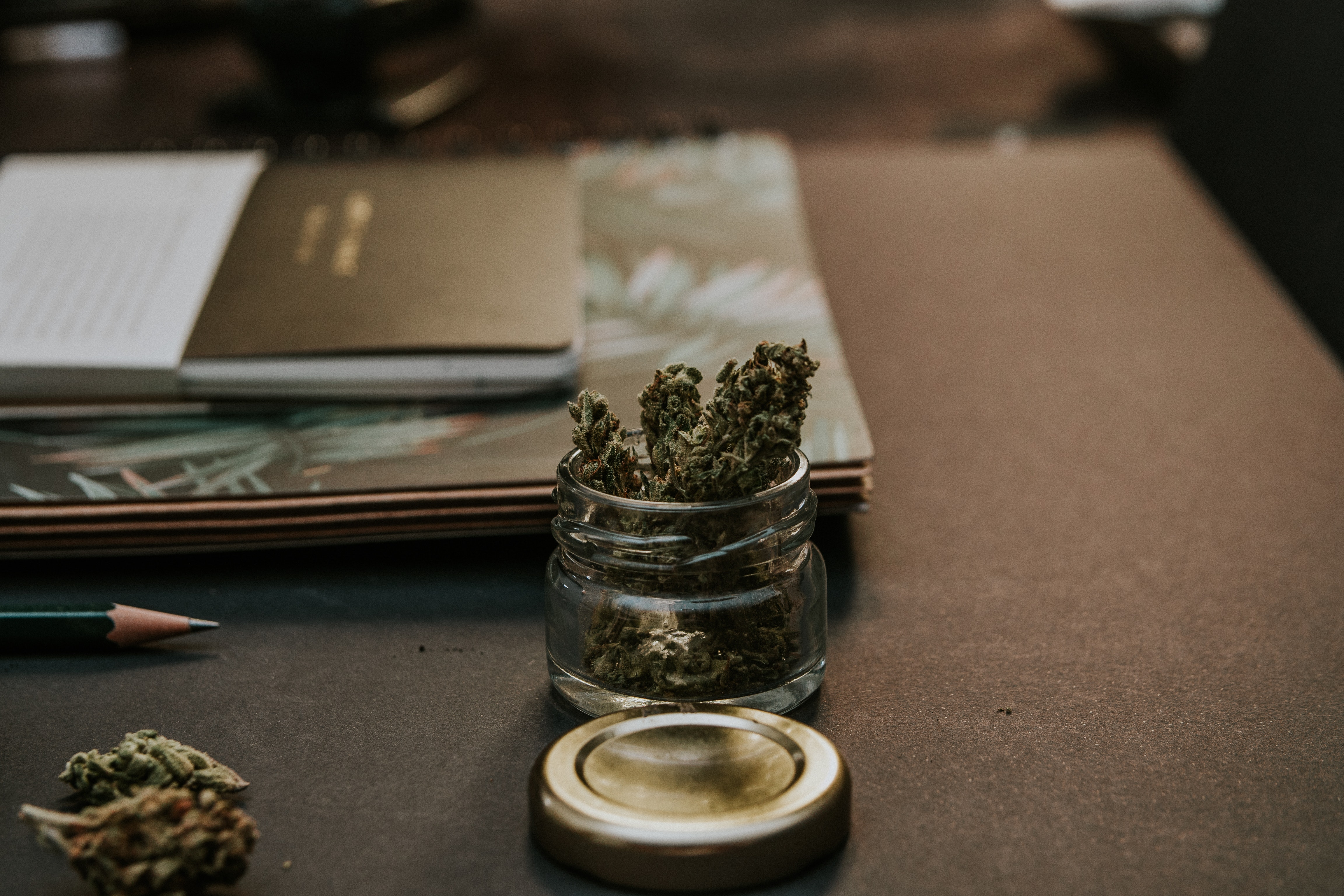 Cannabis in a jar next to a desk and papers